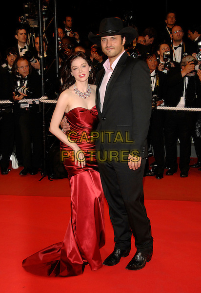 """ROSE McGOWAN & ROBERT RODRIGUEZ.Red Carpet Arrivals at the premiere of """"Death Proof"""" held at the Palais des Festivals during the 60th International Film Festival, Cannes, France, 22nd May 2007..Full length red strapless dress ruched  black suit cowboy hat.CAP/PL.©Phil Loftus/Capital Pictures"""