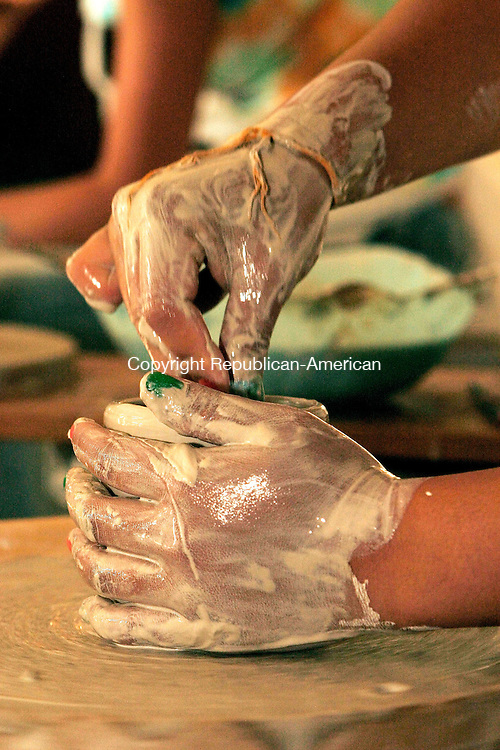 NAUGATUCK, CT - 01 JUNE 2005 -060105JS05--Naugatuck High School Clay III student Arauanh Ackharath gets her hands dirty in clay during a potter's wheel demonstration during the Naugatuck High School art exhibit sponsored by the school's art department Wednesday.   --Jim Shannon Photo--Arauanh Ackharath; Naugatuck High School are CQ