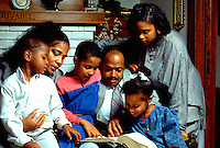 African American family reading Bible in their home with children ages 5 through 15 and parents age 40.  St Paul Minnesota USA