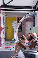 The children of the house relaxing in an Eero Aarnio bubble chair in their play area on the first floor