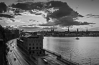 Skymningsmoln över Slussen och Gamla Stan Stockholm med Stadsgådens billed och kaj i svartvitt.