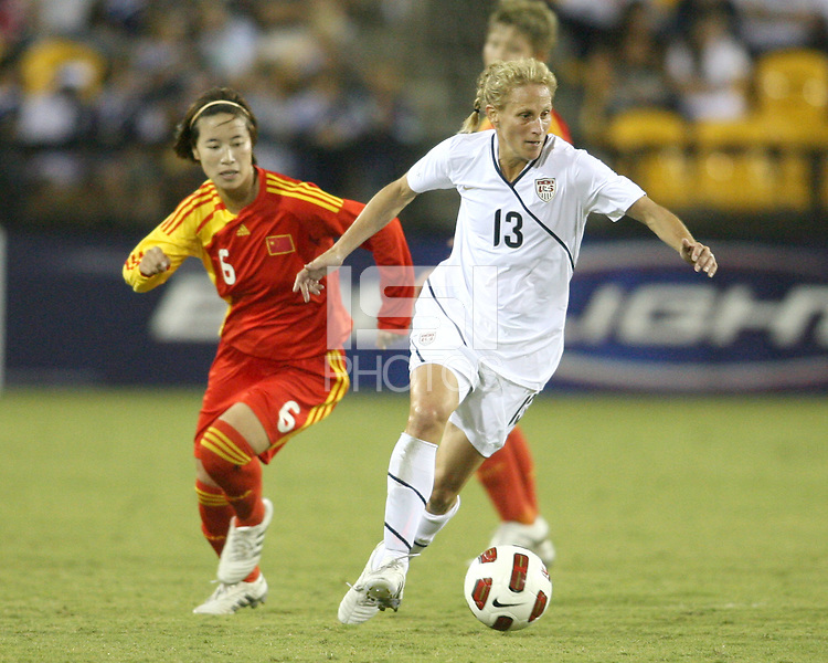 Kristine Lilly #13 of the USA WNT gets away from Na Zhang #6 of the PRC WNT during an international friendly match at KSU Soccer Stadium, on October 2 2010 in Kennesaw, Georgia. USA won 2-1.