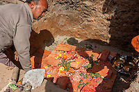 Nepal, Kathmandu, Swayambhunath.  Offerings of Fruit, Flowers, and Vegetables being Placed under the Cornerstone of a Chaitya (Shrine) being Constructed by a Family.