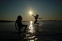 PINARELLO, PORTO VECCHIO, Corsica, France: 03/08/2018: Young children play in the early morning sunrise at la plage du Pinarello (Pinarellu in Corsican) near  Porto Vecchio in Corscia, France, Friday, August 3rd, 2018. Hot air from Africa is bringing a new heatwave to Europe, prompting health warnings about Sahara Desert dust and exceptionally high temperatures that are forecast to peak at 47 degrees Celsius in some southern areas. Photo/Paul McErlane