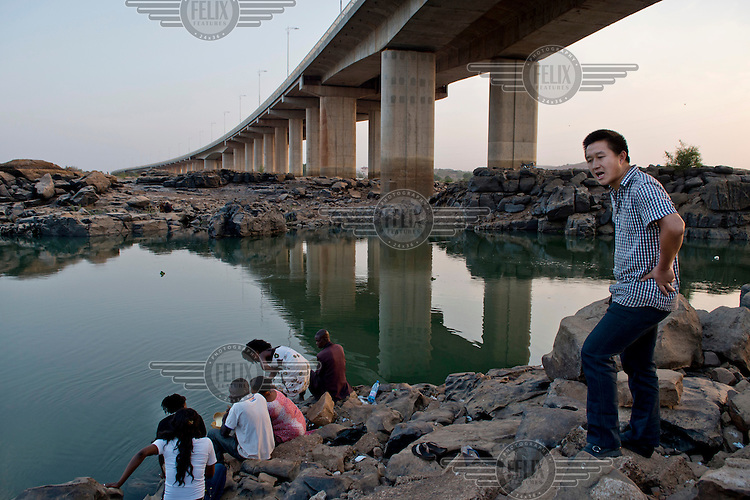 A Chinese man stands on the banks of  the Niger River beneath the Chinese built bridge that was opened in September 2011 and is the third crossing of the Niger in Bamako.