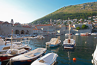The old harbour with small fishing and pleasure boats. The Arsenal and the SRD hill in the background Dubrovnik, old city. Dalmatian Coast, Croatia, Europe.
