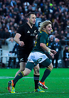Faf De Klerk runs past Ben Smith celebrating victory during the Rugby Championship match between the New Zealand All Blacks and South Africa Springboks at Westpac Stadium in Wellington, New Zealand on Saturday, 15 September 2018. Photo: Dave Lintott / lintottphoto.co.nz
