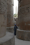 A guide stands beside the columns in the Great Hypostyle Hall in the Precinct of Amun.The hall covers 50,000 sq ft.The roof which has now fallen was supported by 134 columns in 16 rows, the 2 middle rows are higher than the others being 33 feet in circumference and 80 feet high.The hall was built by the Pharaoh Seti I who ruled Egypt from 1290 or 1294 BC -1279 BC and was completed by his son the Pharaoh Ramesses II who ruled from 1279-1213 BC.The obelisk raised by Queen Hatshepsut who ruled from 1479-1458 BC can be seen in the background. Karnak is part of the ancient city of Thebes ( built in and around modern day Luxor).The building of the Temple complex at Karnak began in the reign of the Pharaoh Senusret I who ruled Egypt from 1971 -1926 BC. Approximately 30 Pharaohs contributed to the building of the complex and in so doing made it the largest ancient religious site in the world. The ancient name for Karnak is Ipet-isut (Most select of places).