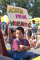Boys age 6 holdings Asian pride worldwide sign at Asian American Festival.  St Paul  Minnesota USA