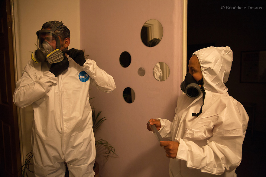"""Donovan and his wife put on their Hazmat suits before beginning a forensic cleaning in the middle-class neighborhood of Colonia del Valle, Mexico City, Mexico on April 26th, 2016. The 65-year-old deceased --who was HIV positive-- worked as a painter, and lived on the roof of the private psychologist's clinic where he had been receiving treatment for depression. His body was discovered in the practice three days after he committed suicide, when hispsychologist was alerted by the odor and the presence of flies. Donovan Tavera, 43, is the director of """"Limpieza Forense México"""", the country's first and so far the only government-accredited forensic cleaning company. Since 2000, Tavera, a self-taught forensic technician, and his family have offered services to clean up homicides, unattended death, suicides, the homes of compulsive hoarders and houses destroyed by fire or flooding. Despite rising violence that has left 70,000 people dead and 23,000 disappeared since 2006, Mexico has only one certified forensic cleaner. As a consequence, the biological hazards associated with crime scenes are going unchecked all around the country. Photo by Bénédicte Desrus"""