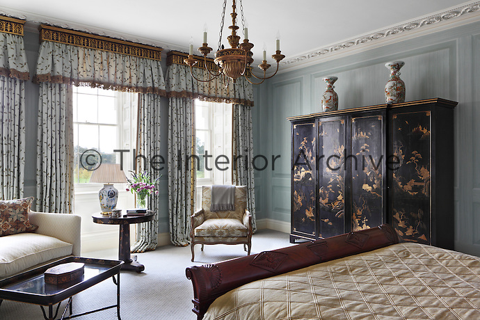 A bedroom painted with blue trompe l'oeil panelling and decorated with gilt embellishments