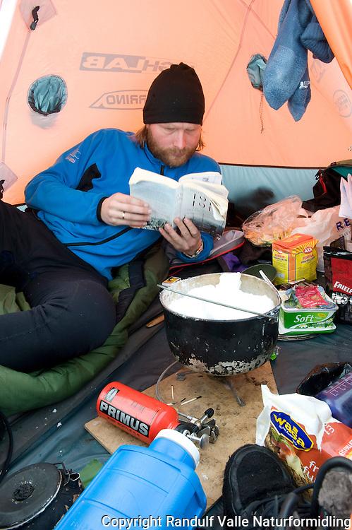 Mann leser bok inne i telt. ----- Man reading book inside tent.