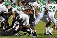 1 September 2011:   FIU's Jonathan Faucher (30) combines with Emmanuel Souarin (24) to bring down North Texas' Brelan Chancellor (80) in the first half as the FIU Golden Panthers defeated the University of North Texas, 41-16, at University Park Stadium in Miami, Florida.