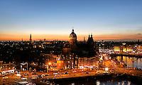 Nederland  Amsterdam 2016 . Amsterdam bij zonsondergang. De Prins Hendrikkade. In het midden de Nicolaaskerk. Rechts het stationsgebied. Foto Berlinda van Dam / Hollandse Hoogte