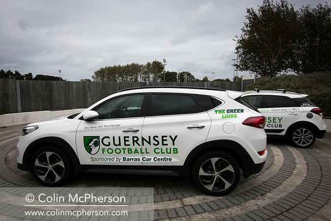 Sponsored cars on display outside the ground as Guernsey take on Corinthian-Casuals in a Isthmian League Division One South match at Footes Lane. Formed in 2011, Guernsey FC are a community club located in St. Peter Port on the island of Guernsey and were promoted to the Isthmian League Division One South in 2013. The visitors from Kingston upon Thames won the fixture by 1-0, watched by a crowd of 614 spectators.