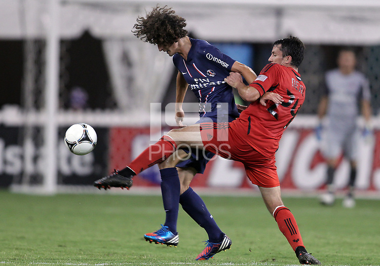 WASHINGTON, DC - July 28, 2012:  Lewis Neal (24) of DC United kicks the ball away from Adrien Rabiot (31) of PSG (Paris Saint-Germain) in an international friendly match at RFK Stadium in Washington DC on July 28. The game ended in a 1-1 tie.