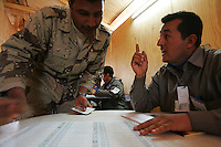 an iraqi official explains the voting procedure to an iraqi soldier from 3d battalion, 1st brigade, 2nd Iraqi Army division before voting in the Iraqi National elections at their base in Camp Rmadi at a pol site under the administration of the Indipendent Electoral Commision of Iraq on Mon Dec 12 2005. At the end of the day about 2000 soldiers will vote at this site according to An Iraqi official.