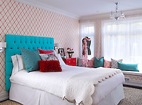 A bold bedroom with red and white patterned wallpaper and a vibrant blue upholstered headboard. The colours and patterns are complimented by the fabrics used to cover the cushions on the window seat.