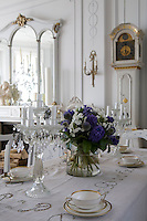 A pair of glass candelabra and a large vase of hyacinths and globe thistles on the dining room table