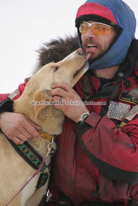 "Lance Mackey hugs his dog ""Scotch"" at the Rainy Pass checkpoint.  Monday, March 7.  2005 Iditarod Sled Dog Race"