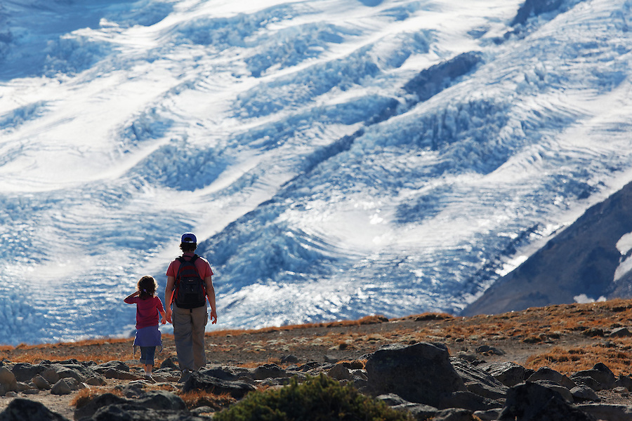 Mother and daughter hikers hiking on First Burroughs Mountain with Emmons Glacier ice in background, Mount Rainier National Park, Washington, USA