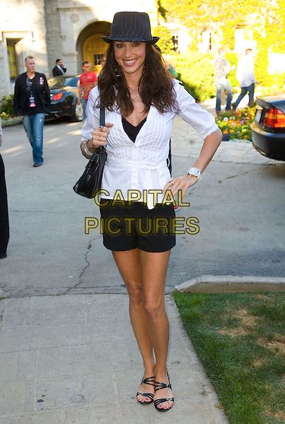 SHANNON ELIZABETH.Aces and Angels Celebrity Poker at the Playboy Mansion, Holmby Hills, California, USA, .11th July 2009..full length white shirt hat trilby shorts black sandals hand on hip bag .CAP/ADM/TC.©T. Conrad/Admedia/Capital Pictures