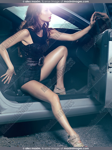 Sexy young woman with beautiful long legs getting out of a luxury car. High fashion photo.