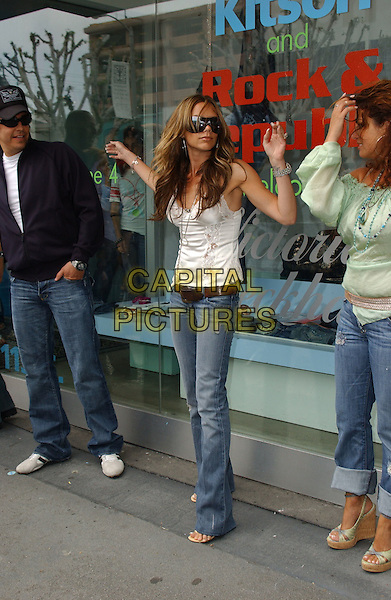 VICTORIA BECKHAM.Promotes her VB Rock & Republic Jeans Collection at Kitson in Los Angeles, California, USA, .June 4th 2005..full length over-sized sunglasses white lace camisole vest top silver necklaces pendant hoop earrings brown belt hands arms up  raised funny.Ref: DVS.www.capitalpictures.com.sales@capitalpictures.com.©Debbie VanStory/Capital Pictures