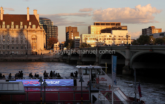 Left bank of the river Thames lit by the late afternoon light, Westminster Bridge (right) and London Boat City Cruise (foreground) in the shade, London, UK. Picture by Manuel Cohen