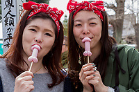 Two Japanese woman eat penis shaped lollipopsduring the Kanamara matsuri or festival of the Steel phallus Kawasaki Daishi, Kawasaki, Kanagawa, Japan. Sunday, April 2nd 2017. The Kanamara Penis festival takes place on the first Sunday of April and celebrates the local legend of a penis eating demon who was defeated after being tricked into biting a steel phallus. The festival is popular with Japan's gay community and now uses its notoriety to raise money for HIV and AIDS charities. It is also wildly popular with foreign and Japanese.tourists.