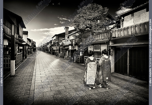 Black and white scenery of Two Maiko, Geisha apprentices in beautiful colorful kimono with long obi walking along empty Hanamikoji Dori street in Gion district in morning sunrise. Hanami-koji, Gionmachi Minamigawa, Higashiyama Ward, Kyoto, Japan 2017. Sepia toned.
