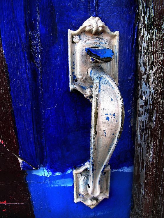 A silver door knocker on a blue door