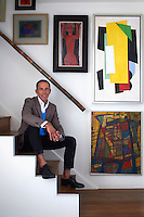 Fashion designer Ben de Lisi sits on the stairs of his London home