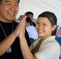 Happy Hmong couple high fiving each other. Hmong Sports Festival McMurray Field St Paul Minnesota USA
