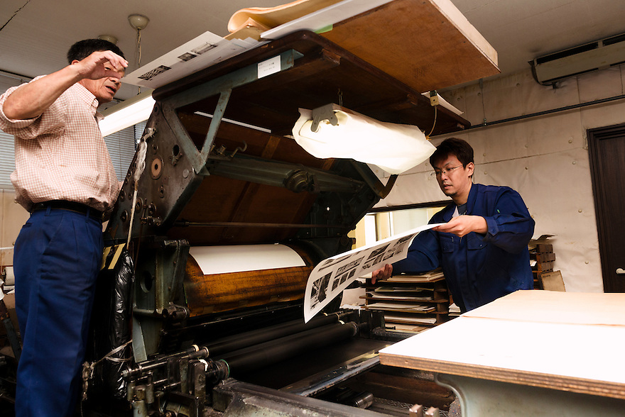 Staff operate a collotype printing press. Benrido collotype atelier, Kyoto, Japan, October 9, 2015. The Benrido collotype atelier in Kyoto was founded in 1887 and is the only full-scale commercial collotype atelier in the world. Collotype is a historic photographic printing process that makes use of plates coated in gelatine. It produces prints of unrivalled quality.