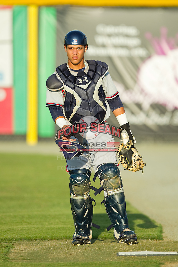 Danville Braves catcher Bryan De La Rosa (26) gets ready to warm up his starting pitcher prior to the Appalachian League game against the Burlington Royals at Burlington Athletic Park on August 16, 2013 in Burlington, North Carolina.  The Royals defeated the Braves 1-0.  (Brian Westerholt/Four Seam Images)
