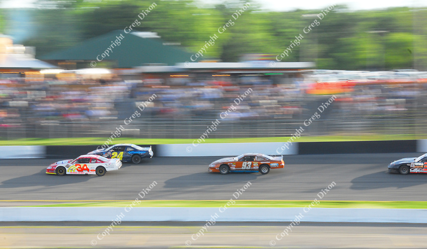 Cars speed past the crowd Saturday night at Dells Raceway Park.