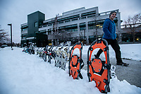 Cooper Hanson preps snowshoes as Physical Ed Professional students and faculty from Outdoor Leadership Theory and Practice (PEP A365) prepare to host snowshoe games on Cuddy Quad after the first major snowfall of the season at UAA.