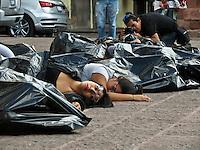"""Querétaro, Qro. 8 de marzo 2016. Colectivos, activistas y organizaciones de la sociedad civil se manifestaron hoy frente a Palacio de Gobierno a través de un performance exigiendo un alto a los feminicidios en el estado. Mujeres permanecieron en el piso metidas en bolsas de basura frente a la consigna """"Feminicidios: Crímenes de Estado"""". Asimismo, se dio lectura a los casos de las 25 mujeres que desde 2015 han sido asesinadas. Foto: Alejandra L. Beltrán / Obture Press Agency"""