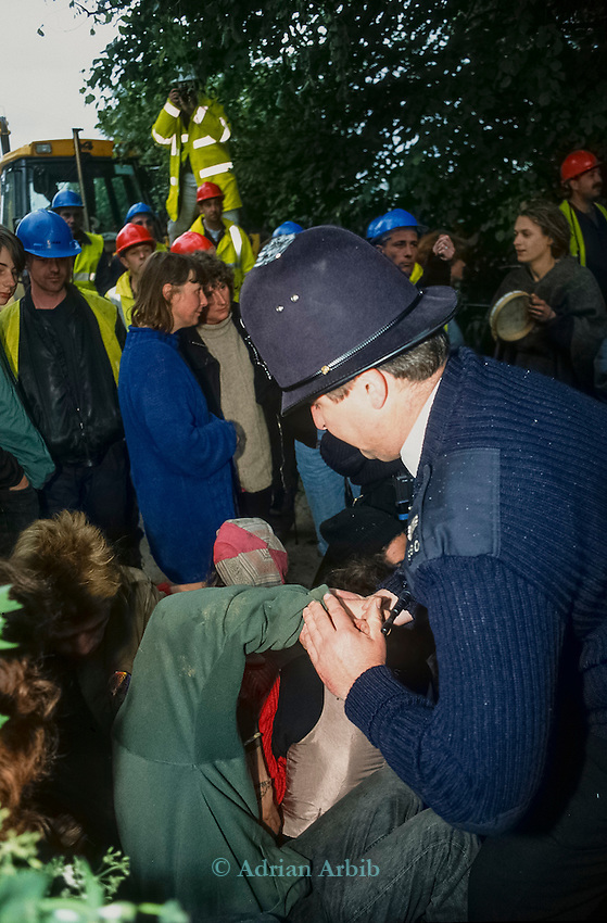 A policemans uses a thumb twist to remove a protester from blocking the road. Solsbury Hill road protest.