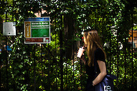 A woman walks next to a community garden organized to produce organic food at Brooklyn in New York,  May 10, 2013, Photo by Eduardo Munoz Alvarez / VIEWpress.