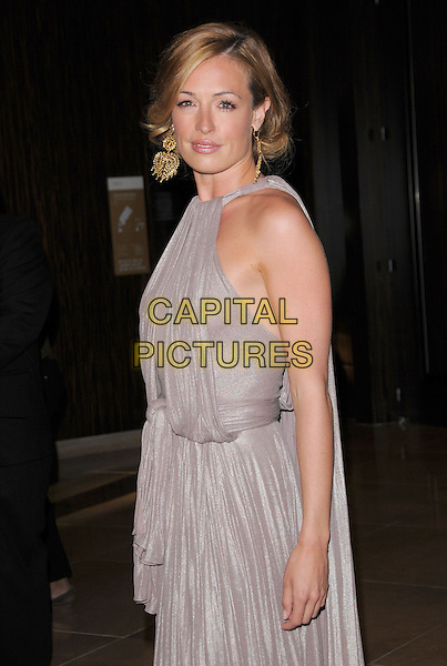 CAT DEELEY.The Gracie Awards Gala held at The Beverly Hilton Hotel in Beverly Hills, California, USA..May 25th, 2010           .half length draped dress gold dangling earrings beige grey gray purple greige sleeveless side .CAP/RKE/DVS.©DVS/RockinExposures/Capital Pictures.