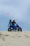 Young couple on custom ATV on dune horizon looking back