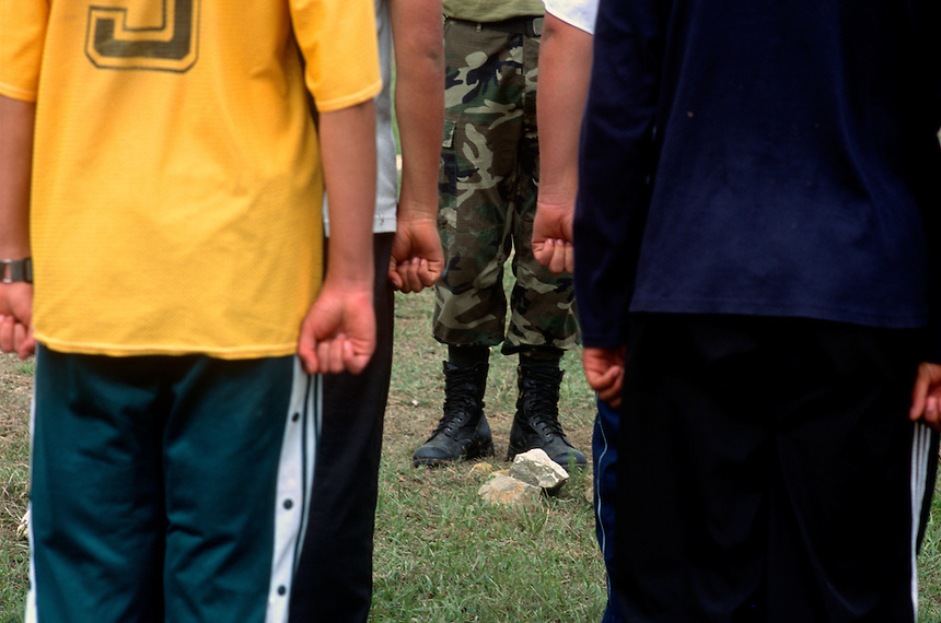 """Bolivian students form up during premilitary training to prepare them for compulsory military service in Vallegrande, Bolivia Saturday, Nov. 13, 2004. The young potential soldiers paraded only two hundred yards from where the body of the executed Ernesto """"Che"""" Guevara lay burried with six fellow guerillas for 30 years. A mausoleum now stands over the open mass grave. Just as nearby, the bodies of twleve more guerillas in Guevara's band were burried on the grounds of a local Rotary Club. The remains were repatriated to Cuba after their discovery in 1997. Guevara was captured by the Bolivian army in 1967 in a nearby valley and executed in La Higuera days later. Guevara and fellow communist guerillas were attempting to launch a continent-wide revolution modeled on Guevara's success in Cuba in the late 1950s. The Bolivian government recently began promoting the area where he fought, was captured, killed and burried for 30 years as the """"Ruta del Che,"""" or Che's Route. (Kevin Moloney for the New York Times)"""