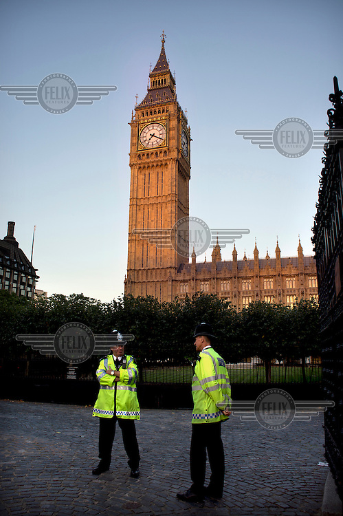 Two policemen on guard at one of the entrance gates that lead from Parliament Square to the Houses of Parliament in Westminster, London.