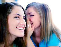 2 teenage girls telling secrets, smiling and laughing.