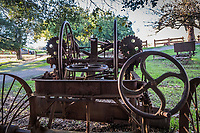 Rolling wheels, steering wheels, gears and more wheels on an ancient farm implement displayed at Garin Regional Park.