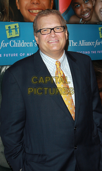 "DREW CAREY.Alliance For Children's Rights ""Right To Laugh"" Fundraiser  held at the Catalina Jazz Club, Hollywood, California, USA..March 15th, 2010.half length black suit jacket yellow gold tie glasses smiling .CAP/ADM/TC.©T. Conrad/AdMedia/Capital Pictures."