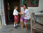 "Ferianus Laia, 9, gets dressed for school with help from his mother, Damaria Halawa, at the doorway of their house in Tugala, a village on the Indonesian island of Nias. The village was struck by both a 2004 tsunami and a 2005 earthquake, leaving houses destroyed and lives disrupted. The ACT Alliance helped villagers here to construct new homes and latrines, build a potable water system, open a clinic and schools and get their lives going once again. For the residents of Tugala, the post-disaster mantra of ""build back better"" became a reality with help from the ACT Alliance."