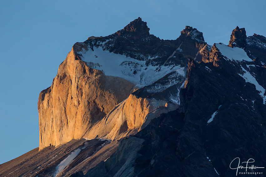Sunset light on the yellow granite face of Monte Almirante Nieto.  Snow caps the black sandstone overlaying the granite layer.  Torres del Paine National Park in Patagonia, Chile.  A UNESCO World Biosphere Reserve.